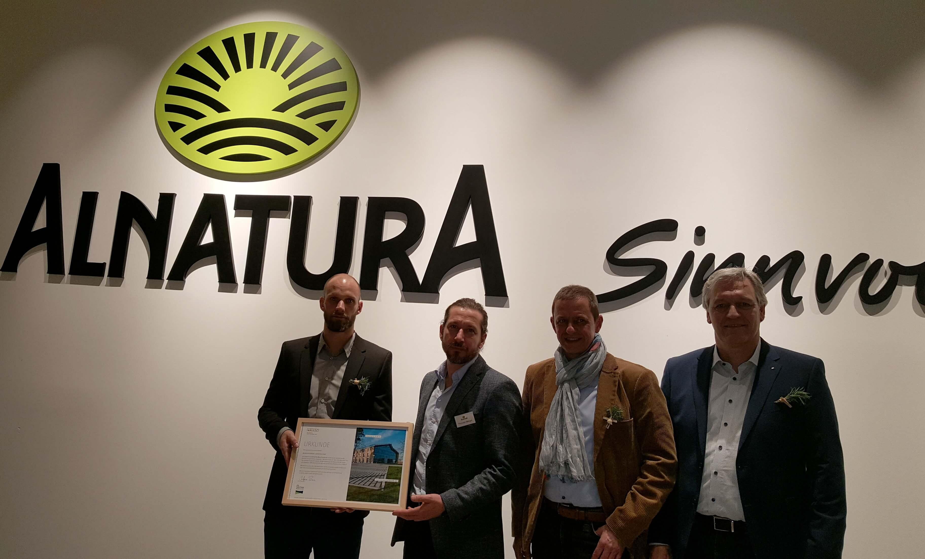 Gruppenfoto von der Eröffnungsfeier mit Rinn-Mitarbeitern und dem Alnatura Betriebsverantwortlichen Expansion und Immobile Thorsten Mergel.